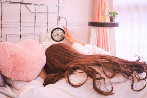 「パジャマ」「ピンク加工」「ベッド」「低血圧」「女性・女の子」「時計」「朝」「部屋」などがテーマのフリー写真画像