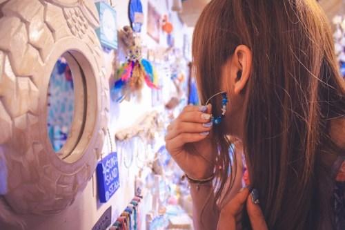 お店の鏡でピアスを耳にあて付けた感じを確認している女の子