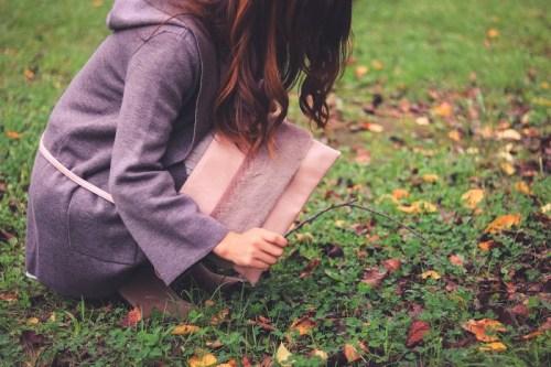 木の枝で秋のカラフルな地面をツンツンする女の子