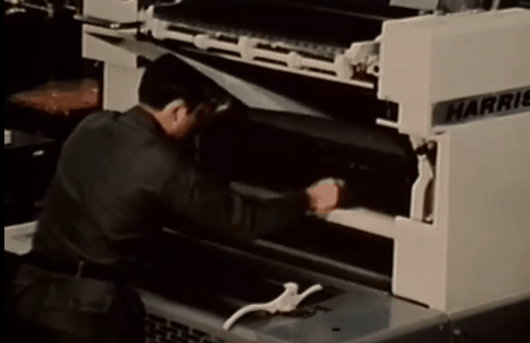 Loading a plate into the reproduction machine in order to make color copies of maps.