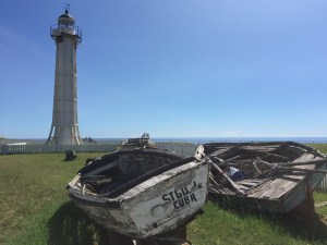 The abandoned lighthouse with some of the old boats that people used to defect to the base.
