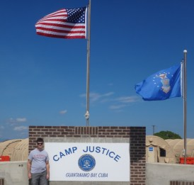 Tyler Smith, standing in front of the sign at Camp Justice, the site of military commissions held in Guantanamo Bay, Cuba