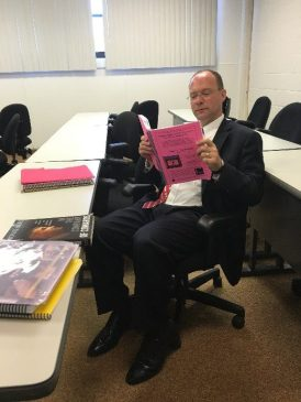 Dean Klein reading a copy of the Guantanamo Bay Fair Trial Manual -- Volume I.