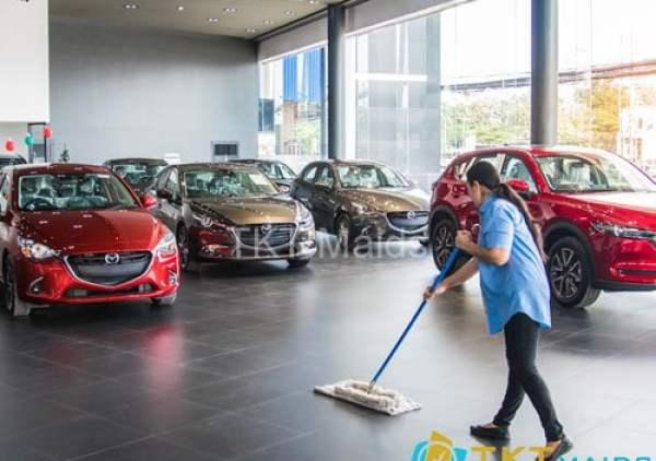 Nhân viên vệ sinh sàn nhà tại showroom ô tô