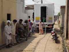 Patients queuing behind the mobile clinic