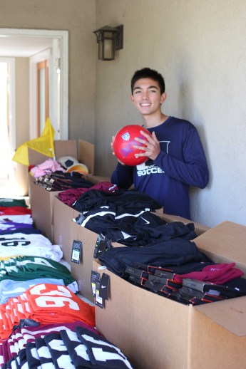Evan Mouchard standing among boxes of soccer equipment.