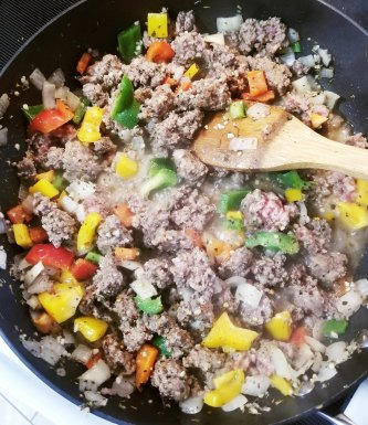 Grass-fed ground beef, Italian sausage, and other ingredients softening
