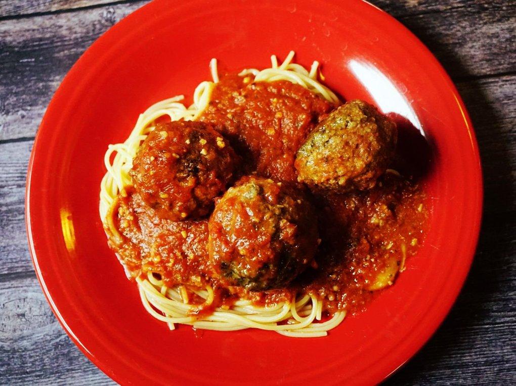 A big plate of mozzarella stuffed meatballs served over spaghetti noodles