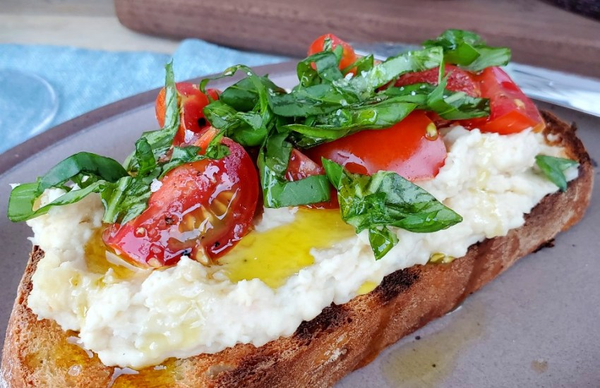 White Bean + Roasted Garlic Puree on Grilled Bread topped with tomatoes and basil