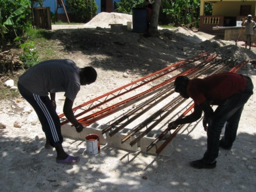 Julio and Blanco priming the bare metal trusses