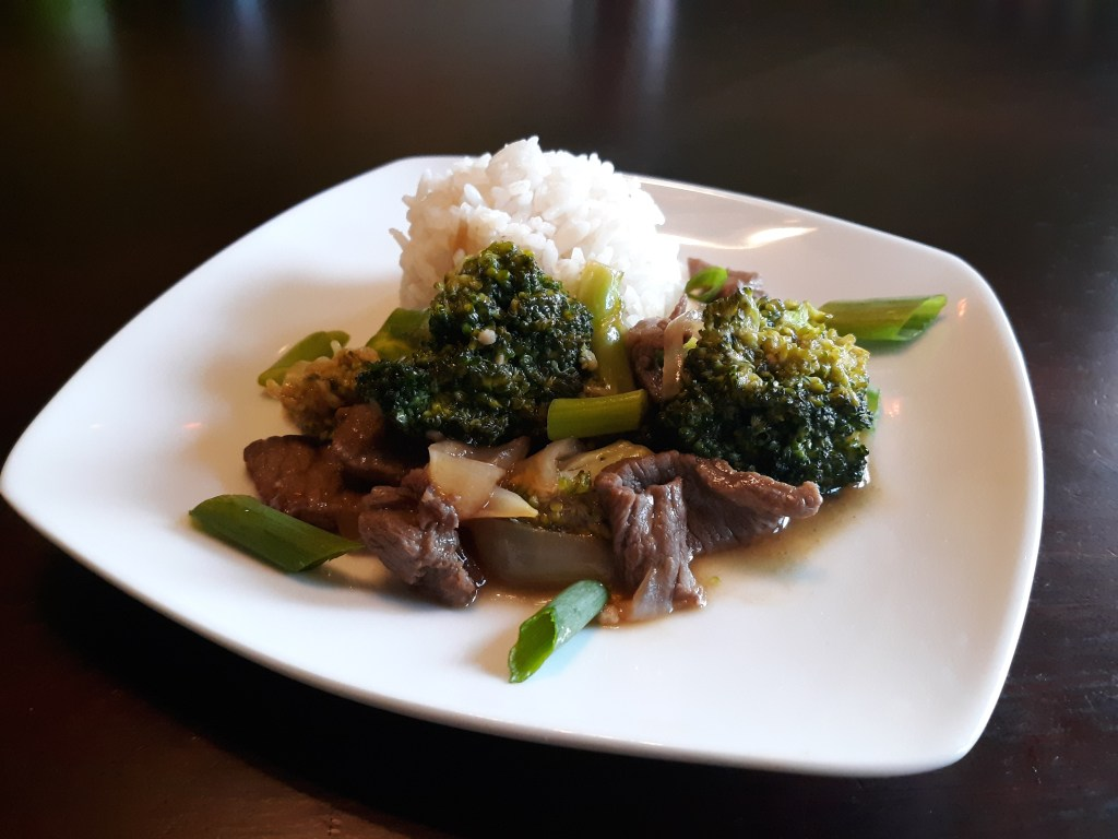 A plate of thinly sliced beef and broccoli next to a mound of white rice, topped with sliced green onions