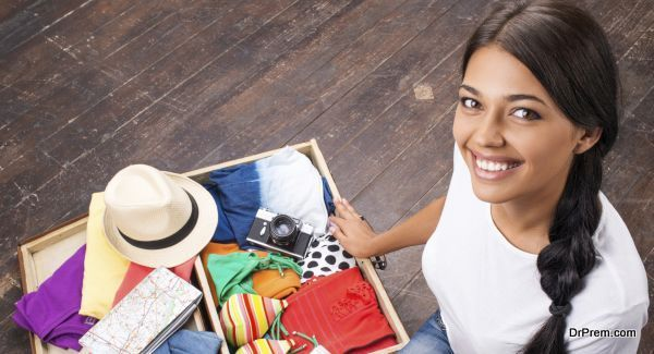 Smiling girl sitting on the floor and checking her suitcase