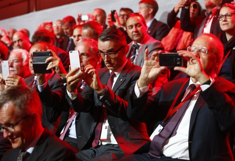 Guests use their mobile devices during the opening ceremony of the NEAT Gotthard Base Tunnel,  near the town of Erstfeld, Switzerland, Wednesday, June 1, 2016. The construction of the 57 kilometer long tunnel began in 1999, the breakthrough was in 2010. After the official opening on June 1, the commercial operation will start in  December 2016. (Ruben Sprich/Pool Photo vi AP)