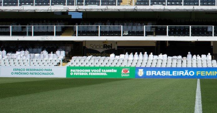 """Foto do campo de futebol do estádio do Santos FC. Na imagem se vê uma placa de Guaraná Antarctica com os dizeres: 'Espaço reservado para o próximo patrocinador. Patrocine você também o futebol feminino.""""."""