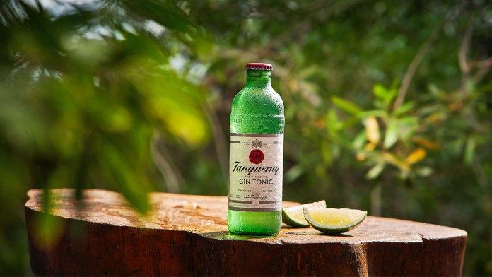 Uma garrafa de Tanqueray & Tonic ao lado de fatias de limão