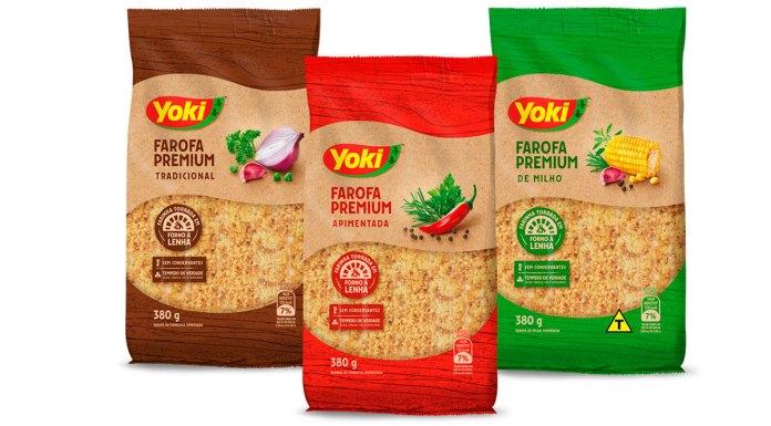 Foto de divulgação da linha de farofa premium da Yoki. Na foto da esquerda para a direita: farofa premium tradicional, apimentada e milho.