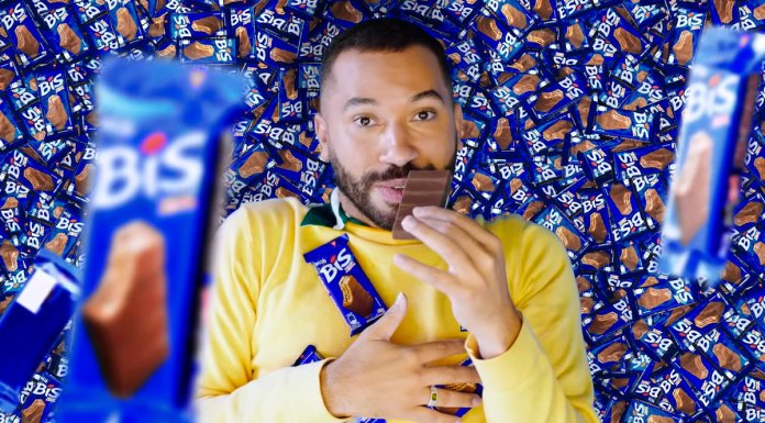 Nova campanha de Bis Xtra com Gil do Vigor. A foto apresenta o Gil deitado em meio a um monte de Bis Xtra, enquanto cai mais chocolate em cima dele e come um dos tabletes.