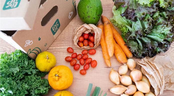 Foto de divulgação do mercado online da Liv Up. A foto apresenta uma mesa de madeira cheia de legumes e verduras espalhas, junto a uma caixa de papelão da Liv Up.