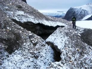 Gdyby przekroić w poprzek jęzor typowego lodowca dolinnego okazałoby się, że ma on kształt wypukły. Dlatego też, woda często kierowana jest do bocznych sektorów jęzora i płynie tuż przy bocznej morenie. Na Svalbardzie moreny te są przeważnie zbudowane z lodu lodowcowego, przykrytego jedynie cienką warstwą gruzu skalnego, osypującego się z przyległych stoków. W rezultacie kanały meandrują również w strefie moreny bocznej. Zdjęcie przedstawia kanały w morenie bocznej lodowca Sven. //Water channel burried in lateral moraine of Sven glacier (Svenbreen). Fot. Jakub Małecki, 2014//