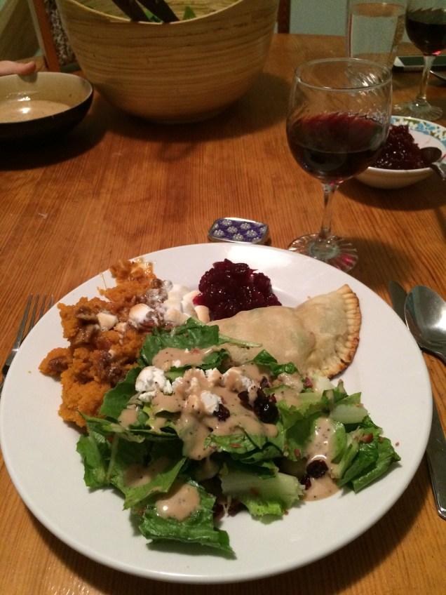 Salad, pot pie, mashed sweet potato casserole, cranberry sauce and wine.