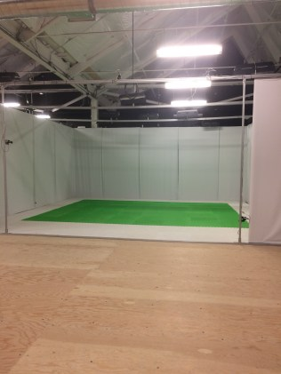 Empty motion capture stage--green flooring enclosed in white curtains