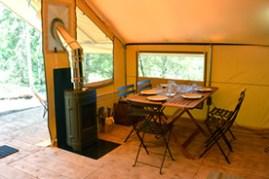 Intérieur de la tente Trappeur avec son poêle à bois au glamping Huttopia à Senonches en Centre Val de Loire