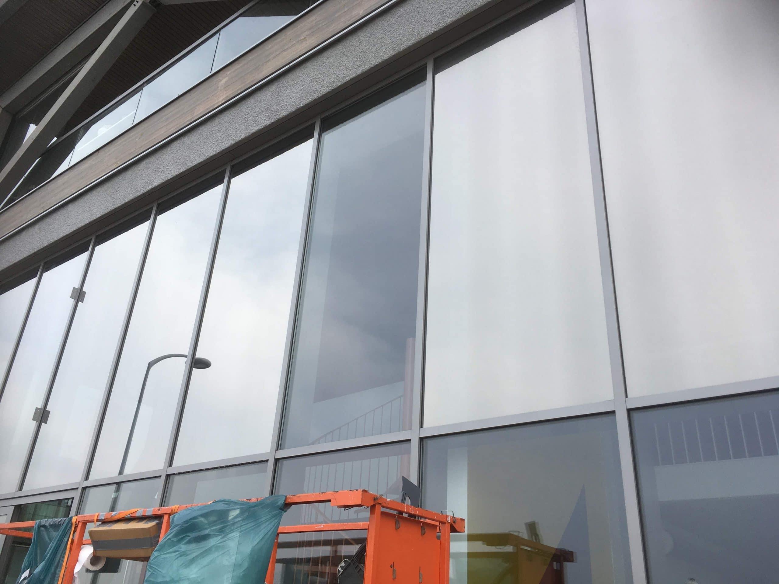 Amsterdam - Sunblock Stainless Steel 25 gemonteerd op de ramen van een bedrijfsruimte om de overmatige zonnewarmte buiten te houden en de hinderlijke schittering te verminderen