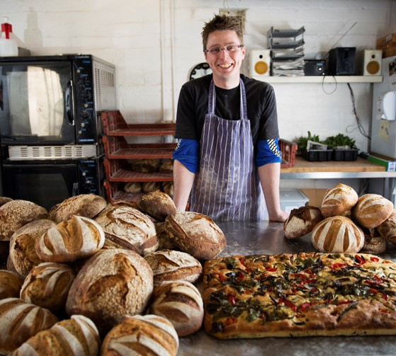 Photo of Andrew standing behind a lot of tasty bread- many loaves and one big foccacia