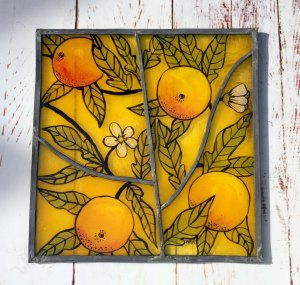 Finished glass panel featuring oranges motif