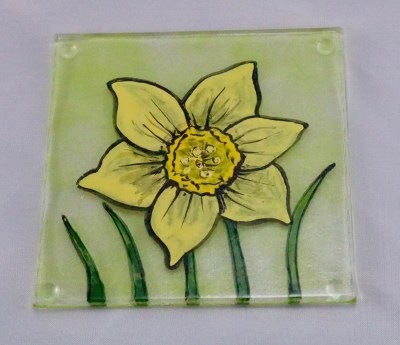 Fused glass coaster of hand painted daffodil on transparent spring green background