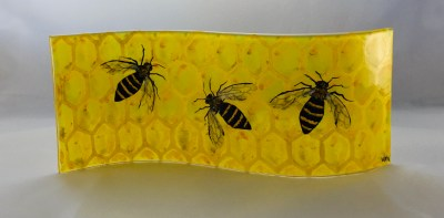 Long wavy fused glass panel of bees on a honeycomb background