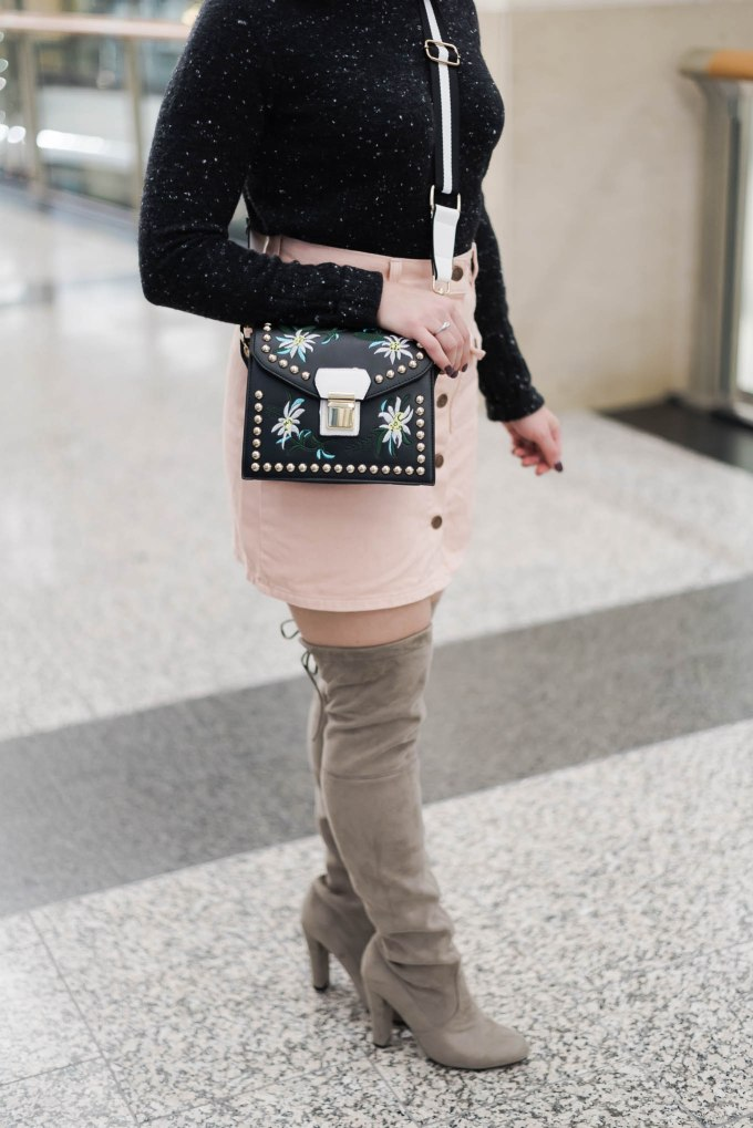 Lifestyle blogger Roxanne of Glass of Glam wearing a MINKPINK denim skirt, otk boots, a Madewell sweater, pom hat, and a rivet crossbody bag
