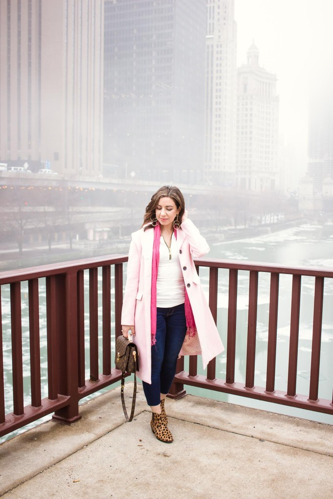 Lifestyle blogger Roxanne of Glass of Glam wearing a Factory-Fashion denim and top, a pink coat, Louis Vuitton Pochette Metis bag, Vince Camuto booties, and Grande Cosmetics lipstick