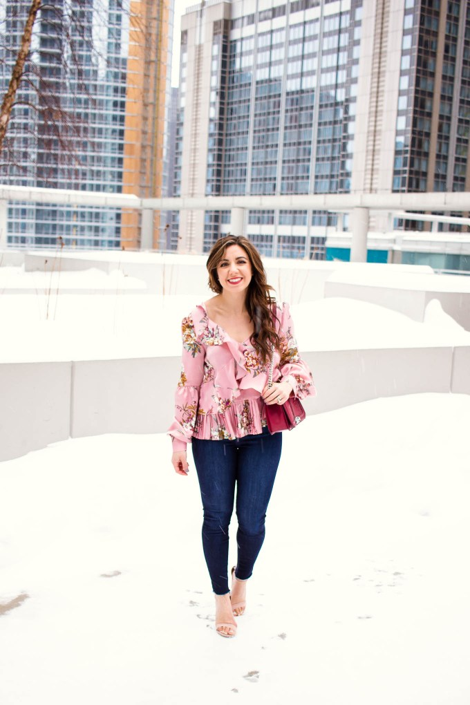 Lifestyle blogger Roxanne of Glass of Glam wearing a Valentine's Day outfit: a Leith pink asymmetrical top, Mott and Bow denim, Justfab heels, and a Rebecca Minkoff bag