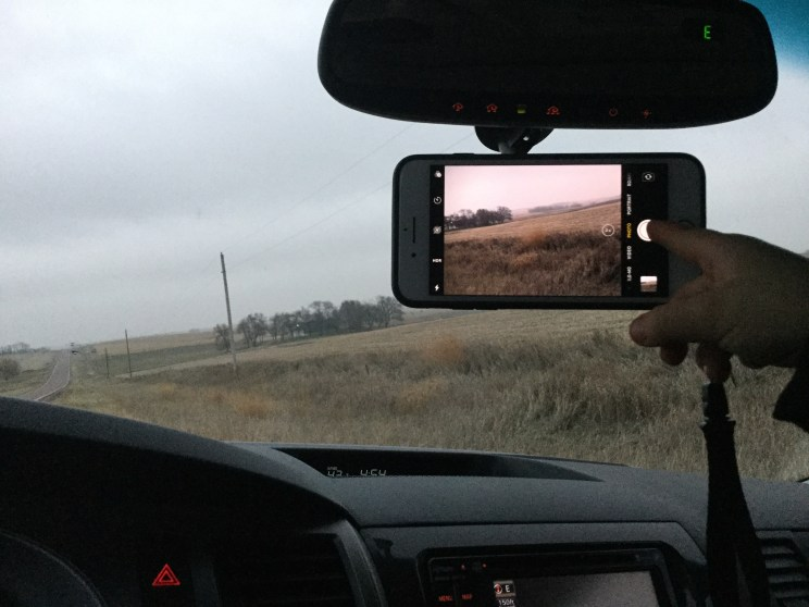 Mount your phone on the dash and ask the front passenger to snap photos when you need them!
