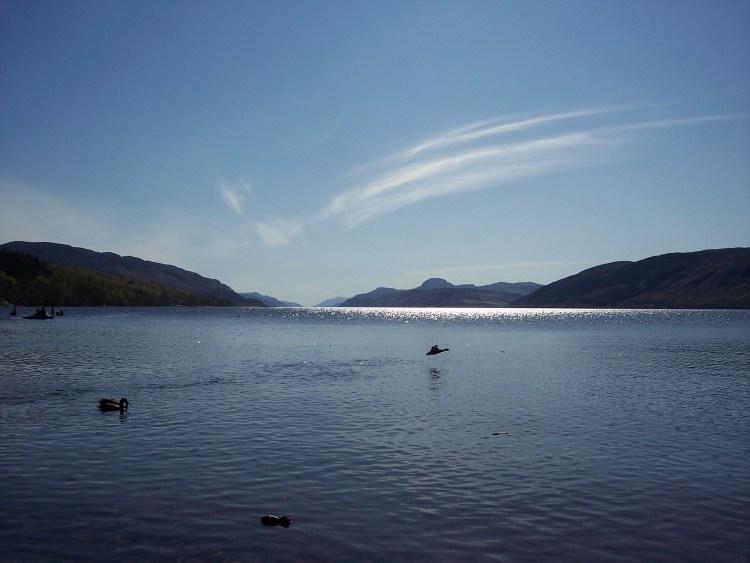 Ducks taking flight above a shimmering Loch Ness