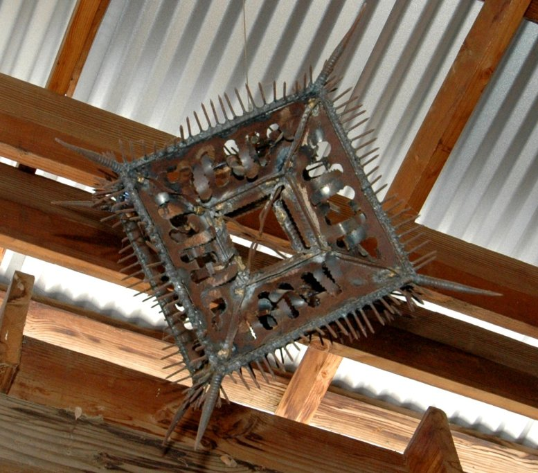 A heavily articulated steel cube with many welded elements