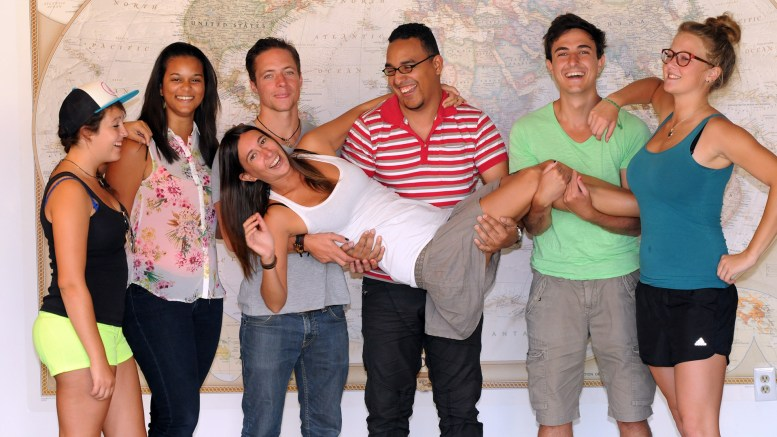 6 people standing in front of a world map, with a 7th person being carried by the group
