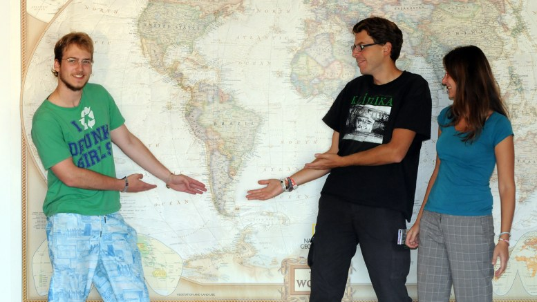 Christopher, Martin & Katerina in front of a world map and pointing to Chile