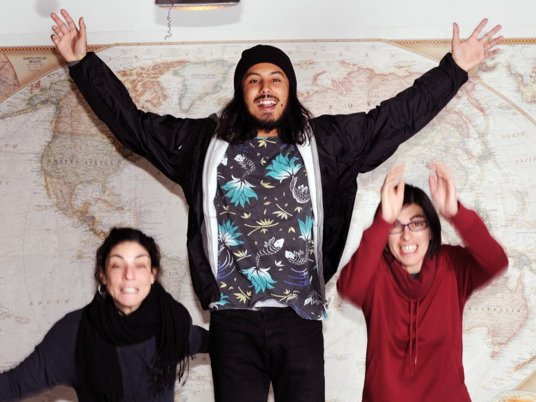 3 people jumping in front of a world map