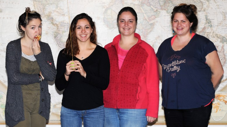 4 people, all from France, standing in front of a large map of the world