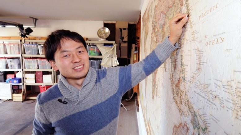"""photo of Tomo Ono pushing a """"Country #25"""" pin into a world map. His pin is at Yokohama, Japan"""