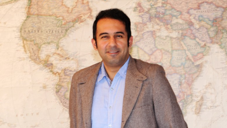 photo of Amir Yazdanbakhsh standing in front of a world map