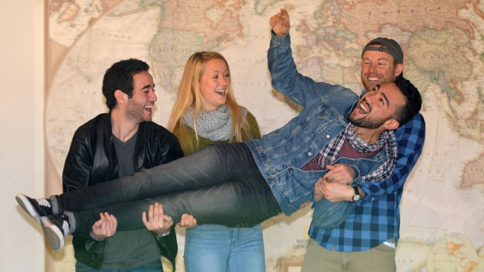 Iheb, Bianca & Mike carry Marouen in front of a large world map
