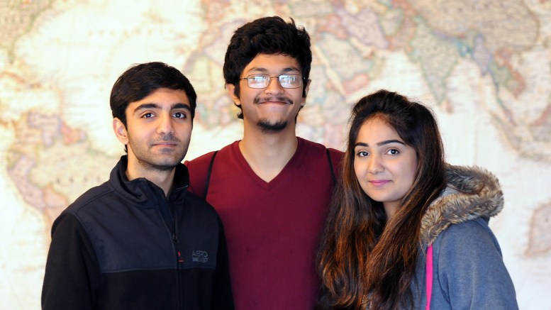 Waleed Ali, Saeef Alam & Sahar Ali standing in front of a large world map