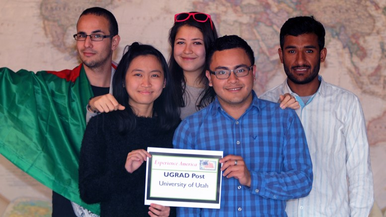 """Mehdi, Yin Chien, Aylar, Jimmy & Sagar standing in front of a large world map and holding a sign that reads """"Experience America, UGRAD Post, University of Utah"""" Mehdi is wearing the Algerian flag."""