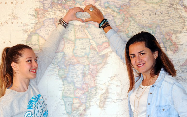 Pinar & Gizem in front of a large world map and making a heart shape around Turkey with their hands