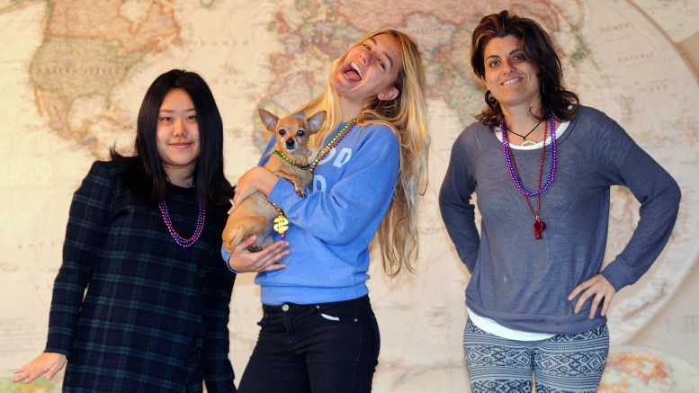 """Blaire, Tiki, Dasha & Silvana in front of a large world map. They're all wearing """"bling"""" like Mardi Gras beads"""