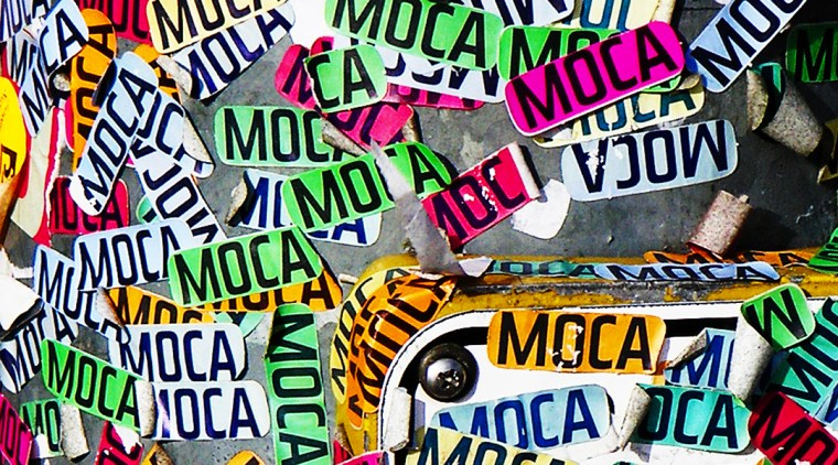 "dozens of ""MOCA"" stickers on a street pole"