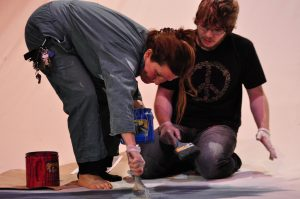 photo of teacher and student working on a large painting on the ground